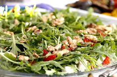 Die Erdbeeren und Rucola putzen. Erdbeeren in kleine Stücke schneiden, Feta in grobe Würfel schneiden. Für die Salatsoße das Öl mit Senf, Balsamico und Ahornsirup gut zusammenrühren, mit Salz und Pfeffer würzen. Den Salat mit der Soße anmachen und die Walnüsse darauf verteilen.