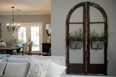 Architectural pieces like these arched window frames and galvanized metal planters are among the decorative enhancements Joanna brings to the new decor. Living At Home, Living Room Art, Living Room Furniture, Living Spaces, Basement Furniture, Small Living, Old Wooden Doors, Wood Doors, Barn Doors