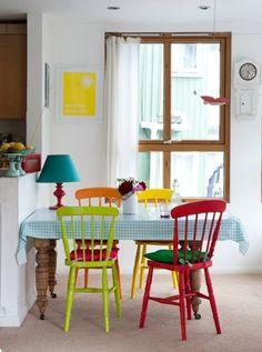 Mesa de madeira branca com cadeiras coloridas