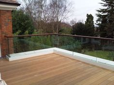 STRUCTURAL GLASS BALUSTRADE TO BALCONY WITH WALNUT HANDRAIL.