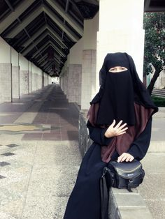 Niqabi Sitting on a Stone Wall