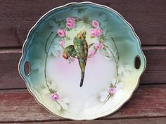 "Here is a Stunning Art Deco Era Hand Painted CT Silesia Altwasser Double Handled Charger plate with 2 Beautiful Parrot Birds perched on a branch, surrounded by pink flowers, gold trim around edge. Measures 10 3/4"" x 9 3/4"". 
