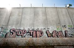 "QALQILYA, OCCUPIED PALESTINIAN TERRITORIES - NOVEMBER 2: The graffiti slogan ""Stop the Wall"" is painted on the Israeli separation barrier's 8 meter tall concrete wall around the West Bank town of Qalqilya."