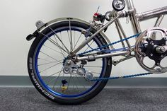 Brompton Roadrunner, metallic tensioner, mudgard wheel, blue chain, chrome eazywheel and rear shock.