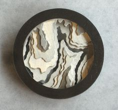 Caitie Sellers topographic brooch – Sterling Silver.  The inside of this brooch is composed of 5 pierced disks to make that image. The top of the brooch screws off so the wearer can take out the slices and do something else with them