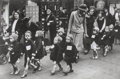 Children from a nursery school in Kentish Town, London, are evacuated. Notice their labels.Previous