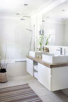 12 salles de bains blanches pour s'inspirer le style zen de cette salle de bains blanche amené par le tapis de style ethnique et les plantes vertes qui en plus d'être déco, contribuent à apurer l'air. Rajoutez quelques galets et touches de bois pour une ambiance exotique assurée.