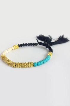 A gorgeous statement bracelet with featured turquoise beads, it has lovely gold thread and little black tassels to finish it off. Grab a few and make a stack.