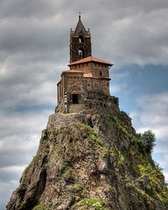 St Michel D'Aiguilhe Chapel, Le Puy, France - a fascinating little pilgrimage chapel perched atop a needle (aiguilhe) of rock in Le Puy-en-Velay, Auvergne. Jutting dramatically towards heaven, the rock needle has been a sacred place for thousands of years: a prehistoric dolmen was built there and the Romans dedicated it to Mercury before the Christians built a chapel to St. Michael.
