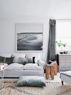 White space. Subtle shades of blue and grey are carried out in the cushions, curtains and art on the wall for easy redesign when you're tired of it (or renting the apartment)