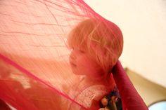 child under red fabric at tipi wedding in essex