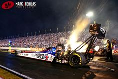 Canon 1Dx, 24-70mm, 10000iso, f4.5, 1/400th, Manual Sparks and flames por out the header pipes as NHRA top fuel driver Antron Brown floors the gas during qualifying for the US Nationals at Lucas Oil Raceway.