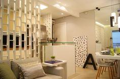 Painel com elemento vazado da a sensação de ser um ambiente único ao apartamento pequeno, dando uma amplitude com a ajuda dos espelhos e elementos claros.