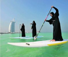 Paddle-boarders from the Surf Dubai club take to the water off Umm Suqeim beach in Jumeirah yesterday wearing abayas and kanduras, as part of an effort to persuade more Emiratis to take up the activity, and enjoy watersports in general.