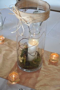 Burlap jute tied w/ raffia lined the top of these tall glass cylinders that contained a candle surrounded by sheet moss, hydrangea blooms, curly willow and black river stones.  Floral Design: Amanda Bowers, Tampa, FL AmandaKayBowers@gmail.com