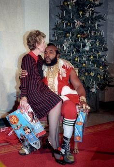 Nancy Reagan kissing Santa Mr. T in front of one of the White House Christmas trees, 1983.