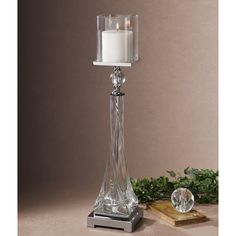 A thick, twisted glass base with polished nickel details and crystal accents make up this beautiful, decorative candle holder. An off-white, distressed candle is included to finishe the piece.