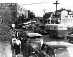 circa 1950 scene in Lynchburg, Virginia | Craddock-Terry Shoe Corp. Fort Hill Plant workers head home at the end of a shift, in a photo taken at the intersection of Campbell Avenue & 12th Street in Lynchburg, Virginia circa 1950. In front of the line of workers is Mrs. Louis Scruggs. Also visible in this photo is the Cities Service gas station on the southeast corner of the intersection. This image is part of the RetroWeb Visual History of Lynchburg, Virginia