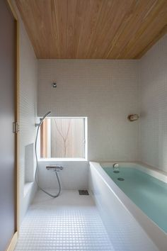 Tiled bathroom with tub and plywood ceiling.