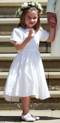 Pictured: An adorable Princess Charlotte cuts a cute figure in a white bridesmaid dress co...