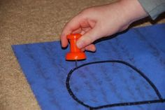 Use of a giant push pin to trace letters on carpet/carpet square.
