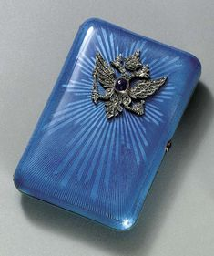 A JEWELLED SILVER-GILT GUILLOCHÉ ENAMEL CIGARETTE-CASE marked Fabergé and with the workmaster's mark of August Hollming, St. Petersburg, 1908-1917, with scratched inventory number 4185. Of rectangular form with rounded corners, overall enamelled in translucent blue enamel over guilloché sunburst ground emanating from a silver-gilt Imperial double-headed eagle set with rose-cut diamonds and a sapphire, with a silver-gilt mounted sapphire thumbpiece.