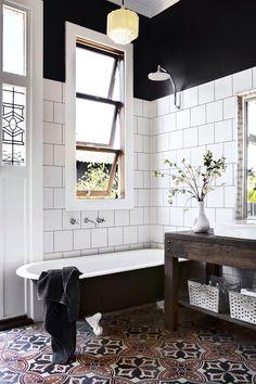 white tile + black paint + pattern flow + clawfoot tub + modern dark wood sink
