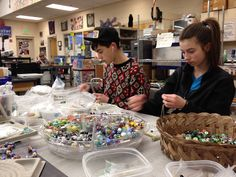 Hilltop Artists production team stringing their own handmade glass beads into beautiful necklaces to be sold in the gallery.  Tacoma, WA