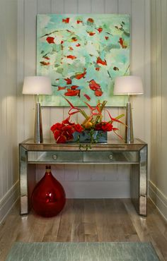 House of Turquoise: Studio M Interior Design Mint and red artwork above console table with the red emphasised by floral arrangement and urn below the the table.