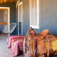 Porche gris country avec baril de pétrole, selle, lit et fauteuil en corde.