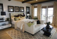 61 Master Bedrooms Decorated By Professionals - The black coffee table and windows allow the bed, which uses lighter colors, to really stand out in this design.
