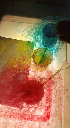 bubble mix and water colours on the light table - as seen by member Katelyn Moon in The Ultimate Light Table Guide Facebook group