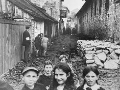 """Szydłów Ghetto appeared in American newspapers in December of 1940. The press caption read, """"The littered street, lined with old brick and stone houses, is in the Szydlow Ghetto. The white arm band on man at left must be worn by every Jew over 10 years old in German occupied Poland."""""""