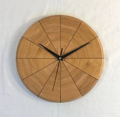 This beautiful segmented wall clock would look great in any room of the house. There is a thin line of black veneer separating each of the twelve segments, giving the clock an elegent, simple look. Three rubber bumpers on the back create an attractive shadow line around the clock