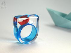 Schiff Ahoi – Maritimer Boote-Ring mit selbst gefalteten Mini-Booten aus roten und weißen Papier auf blauen Ring in Gießharz