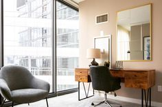 Wooden desk with angular metal legs in modern apartment for rent in Chicago's River North neighborhood. Swivel office chair at wooden writing desk in bright apartment for rent in Chicago makes a neat space for a home office. Gold framed mirror hanging on wall above a wooden desk and beside floor-to-ceiling windows in sunny modern apartment for rent in downtown Chicago | Domu Chicago Apartments