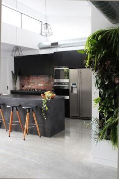 With its polished-concrete floor, recycled-brick splashback, exposed-metal ducting, 4.2m-high ceiling and concrete island, the kitchen at right has serious industrial cred.