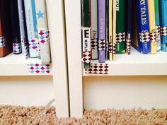 Use patterned washi tape to denote which shelf each book goes on. Even those who are too young to read can put the books back where they belong. Genius!