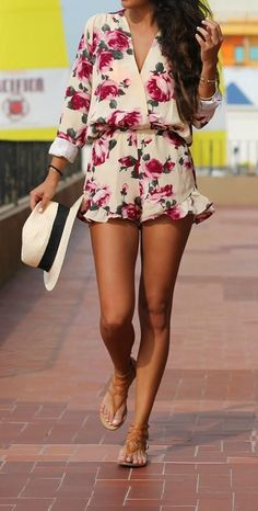 Short floral romper for summer with flat sandals and hat. She looks so comfortable in this outfit. Simple style.