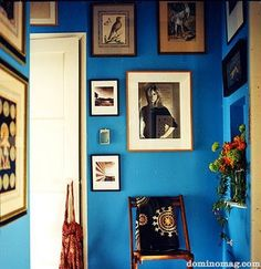 A spaced out collection of wall art on a vibrant blue wall wit wooden frames gives a slightly Bohemian air.