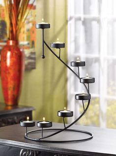 Crown any tabletop with a shimmering spiral of golden light! Matte-black candleholder cradles eight tealight votives in a breathtaking stair-step display. Dramatic alone, or circle around a vase of fr