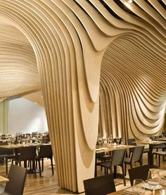 Banq restaurant, located in Boston, wins award and sets the senses swirling with its banyan tree-inspired aesthetic. Curved layers of birch form an abstract wooden canopy above recycled bamboo tables. The restaurant was created within an early 20th century savings bank building that had been long abandoned