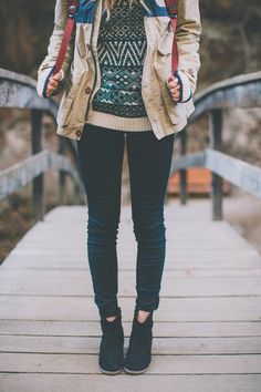 tan jacket with a blue stripe. patterned sweater. black shoes.