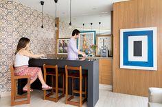 Decoração de apartamento com parede estampada, revestimento de madeira, banqueta de madeira e quadro azul e branco.