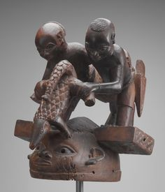 """Asamu, Died circa 1970 Artist: Falola Edun, born 1900 Helmet Mask with Two Male Figures and a Pangolin  mid-20th century Wood, pigment, and nails Overall: 35 x 35 x 30 cm (13 3/4 x 13 3/4 x 11 13/16 in.) Gift of Ellen and Stephen Susman, B.A. 1962 2004.60.1 Gelede masks are made in pairs and danced by men during a celebration honoring elder women and ancestors, fostering social cohesion and harmony, and providing entertainment.  The """"mothers"""" are believed to have both positive and negative…"""