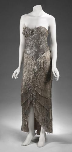 A full-length gown owned and worn by Gypsy Rose Lee, with rhinestones and silver beaded fringe, a strapless sweetheart neckline, front slit, and back zipper closure.  Sold at auction for $ 10,000.