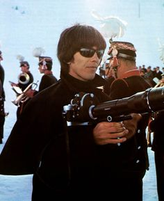 George Harrison using a Trigger Leica camera Judging from the background it looks like this was during the filming of Help! in March of 1965