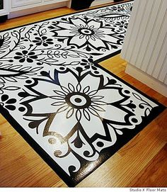 Vinyl flooring turned upside down and painted on to create a floor cloth.  I have created floor cloths this way and I must share it is my favorite over canvas or linen.  The rug is heavy duty and remains flat without carpet tape.  I really like this graphic black and white design.  This design would look great with any color.
