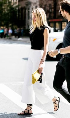 White trousers with a black tank and lace-up sandals.