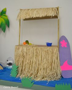 Tiki hut luau decoration. Cost less than $5. Large cardboard box, 3 grass skirts hot glued on, 2 bamboo poles from the garden section and some twine. Surfboard made from cardboard and covered in paper.